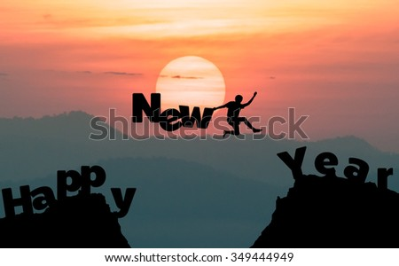 silhouette man jumps to make the word Happy New Year with sunrise