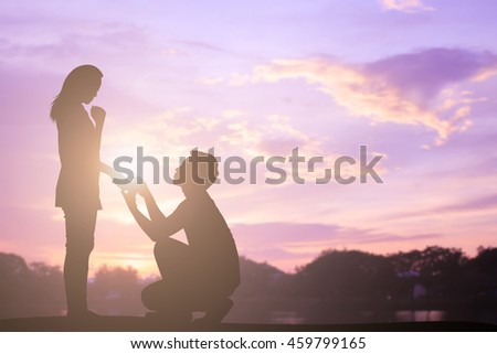 silhouette man kneel for engage woman in sunset hours at park outdoor:asian couple lover concept. - stock photo