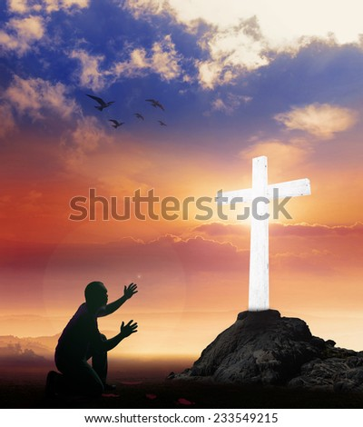 Silhouette man kneeling and raising hands over the white cross on a sunset background. Worship, Forgiveness, Mercy, Humble, Repentance, Reconcile, Adoration, Glorify, Redeemer, Christmas concept.