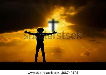 Silhouette man  praying over the cross on beautiful sunset  - stock photo