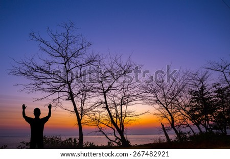 Silhouette man show his hand up in the air with dead tree at sunset beach - stock photo