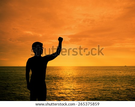 Silhouette man showing his hand at sunset beach - stock photo