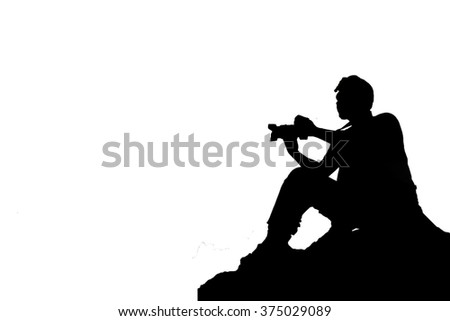 Silhouette man, sitting on the rock, holds a camera with one arm isolate
