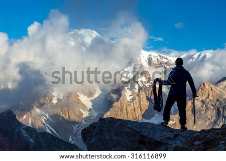 Silhouette Man Staying on Top of Rock Cliff Holding Climbing Gear Stormy Clouds and Peaks Illuminated Morning Sun - stock photo