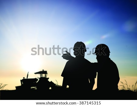 silhouette man survey and civil engineer stand on ground working in a land building site over Blurred construction worker on construction site. examination, inspection, survey - stock photo