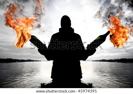 Silhouette man with a molotov cocktail - stock photo