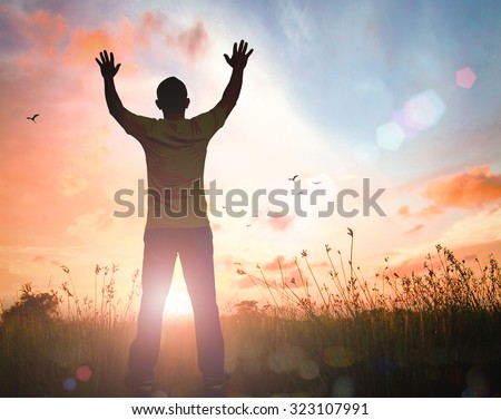 Silhouette man with hand raised to beautiful sunset background. World Mental Health Thanksgiving Dignity Christmas Forgiveness Mercy Humble Repentance Glorify Praise International Mountain Day concept - stock photo