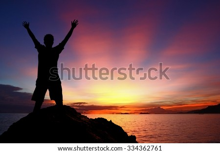 Silhouette man with hands raised standing on the rock at the sea with the sunset background