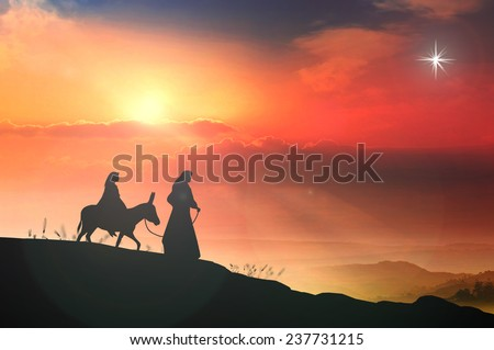 Silhouette Mary and Joseph journeying through the dessert with a donkey on sunset looking for a place to stay on Christmas Eve. - stock photo