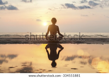 Silhouette meditation girl on the background of the stunning sea and sunset. Yoga, fitness and healthy lifestyle.  - stock photo