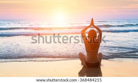 Silhouette meditation yoga woman on the background of the sea and amazing sunset. Yoga silhouette.