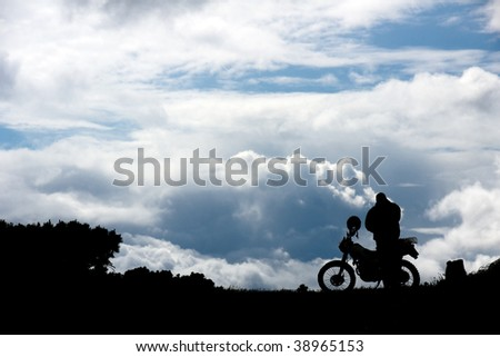 silhouette men near motorcycle on background of the sky - stock photo