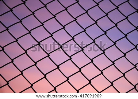 Silhouette mesh steel fence at twilight time