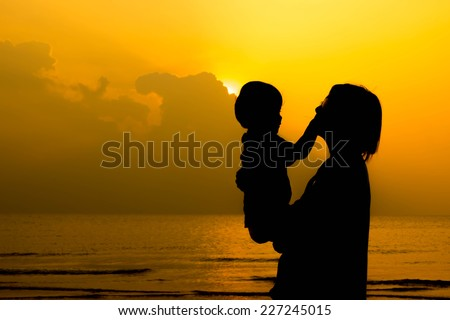 Silhouette mom and baby with sunrise