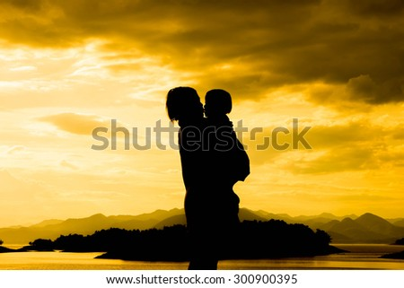 Silhouette Mom and little on sunset background