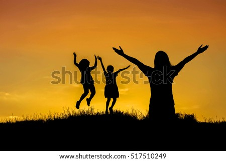 Silhouette mother standing raised hands up and children jumping on sunset .happy time family concept