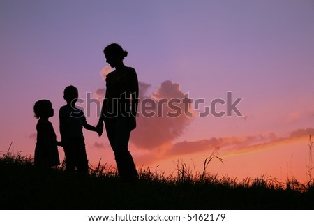 silhouette mother with children on sunset - stock photo