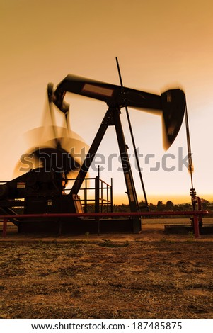 Silhouette Moving Oil Pump Jack (Sucker Rod Beam) During Sunset Time - stock photo