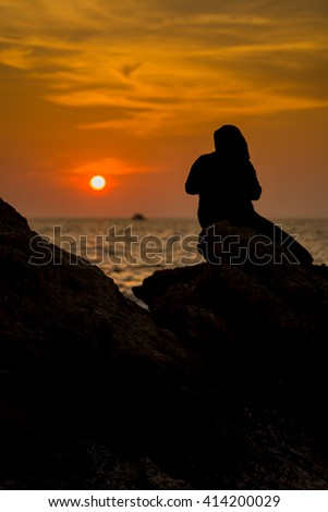 Silhouette Muslimah woman tourist texting on smartphone before sunset on the beach rock , Phuket Thailand.