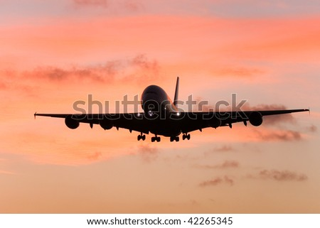 Silhouette of A380 airliner approaching landing at sunset.