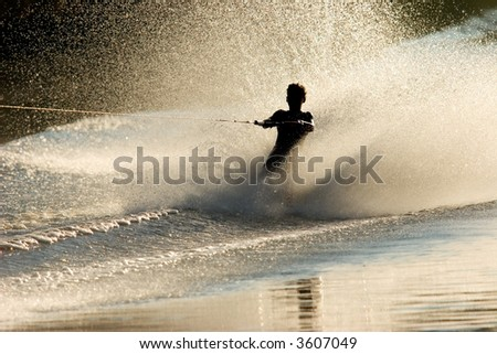 Silhouette of a barefoot skier with backlit water spray