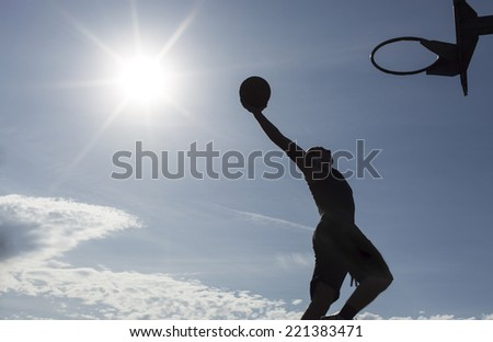 Silhouette of a basketball player in mid air about to slam dunk on a sunny day with the sun in the background - stock photo