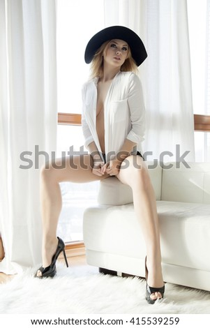Silhouette of a beautiful and sexy young adult sensuality blonde woman in white shirt black hat and panties on the white sofa in luxury apartment - stock photo