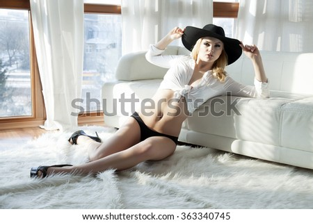 Silhouette of a beautiful attractive and sexy young adult sensuality pretty blonde woman in white shirt black hat and panties lying on the white sofa in luxury apartment - stock photo