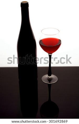 silhouette of a beautiful bottle of wine with a glass - stock photo