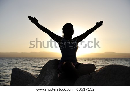 Silhouette of a beautiful female meditating on a rock by the sea - stock photo