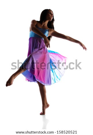 Silhouette of a beautiful female modern jazz contemporary style dancer isolated on a white background. Dancer is barefoot and wearing a blue and purple dress. - stock photo