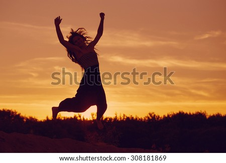 Silhouette of a beautiful girl jumping over sunset - stock photo
