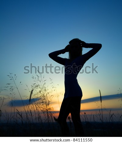 Silhouette of a beautiful girl over sunset - stock photo