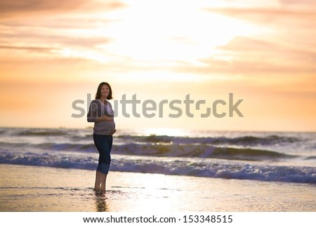 Silhouette of a beautiful pregnant woman walking at the beach on a summer evening at sunset