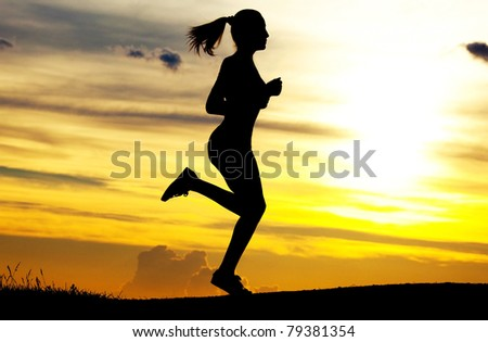 Silhouette of a beautiful running woman against yellow sky with clouds at sunset - stock photo