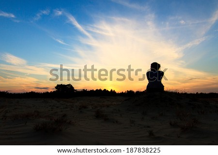 Silhouette of a beautiful woman at sunset in national park Kootwijkerzand in the Netherlands - stock photo