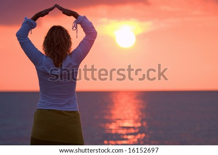 Silhouette of a beautiful woman in a red sunset - stock photo