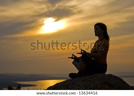Silhouette of a beautiful woman meditating on a rock at the sunset - stock photo