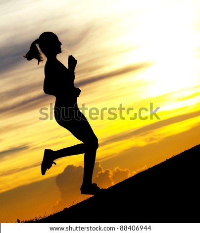 Silhouette of a beautiful woman running up the hill against yellow sky with clouds at sunset - stock photo