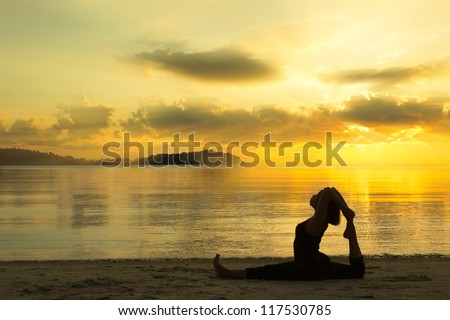 silhouette of a beautiful yoga girl at sunrise on the beach - stock ...
