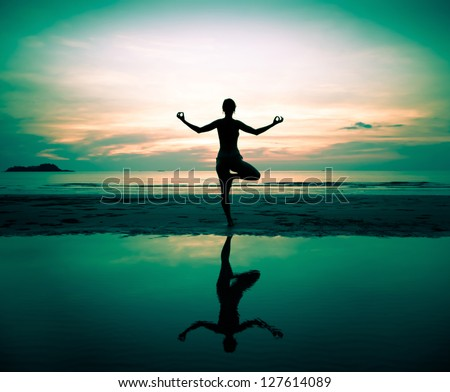 Silhouette of a beautiful yoga woman at sunset (in surreal colors) - stock photo