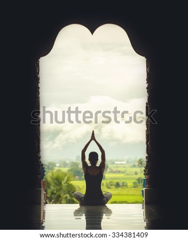 Silhouette of a beautiful Yoga woman in the morning - vintage style color effect