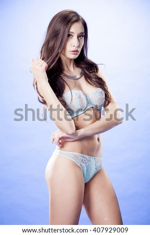 Silhouette of a beautiful young adult slim sexy and attractive sensuality pretty brunette woman in blue erotic lingerie on blue background - stock photo
