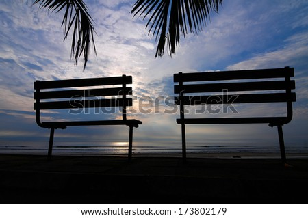 Silhouette of a bench near beach during sunset. - stock photo