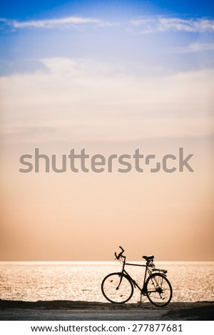 Silhouette of a bicycle in front of the evening sky at the coast/Bicycle at the Coast - stock photo