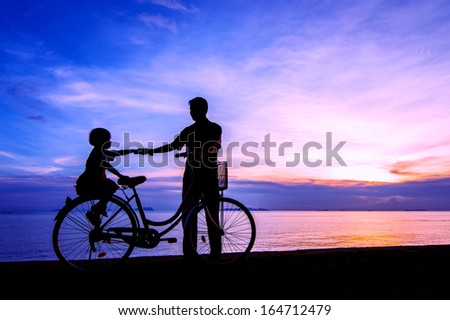 Silhouette of a biker family on the beach at dusk.