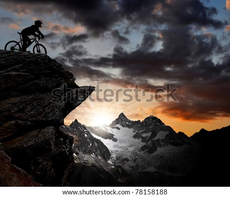 silhouette of a biker in the Swiss Alps - stock photo