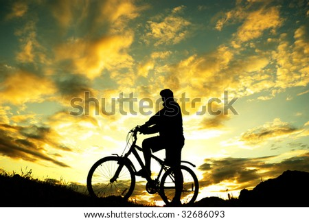 Silhouette of a biker standing - stock photo