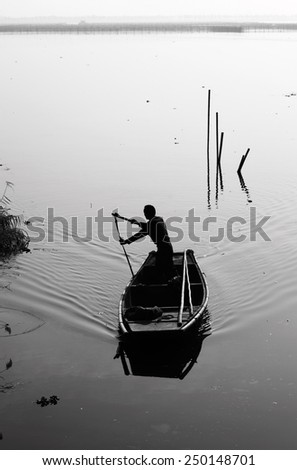 Silhouette of a boatman rowing a traditional wooden boat on a lake, processed in monochrome. - stock photo