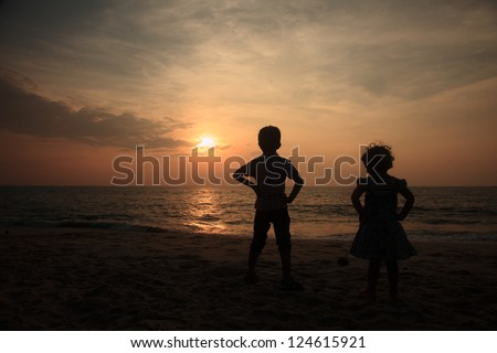 Silhouette of a boy and girl enjoying the sunset in a beach - stock photo